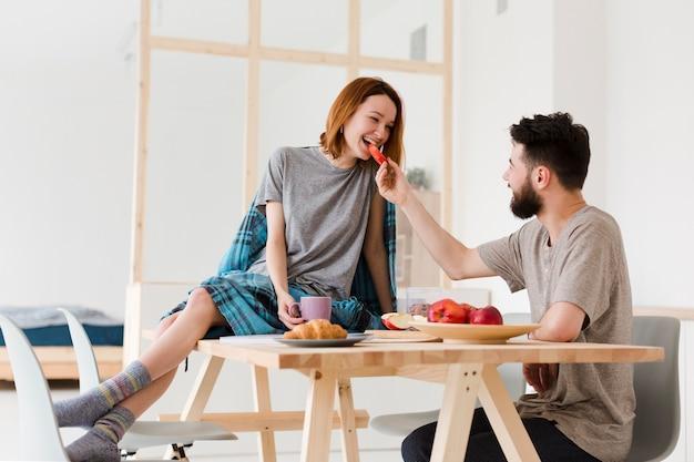Uomo e donna che mangiano in cucina