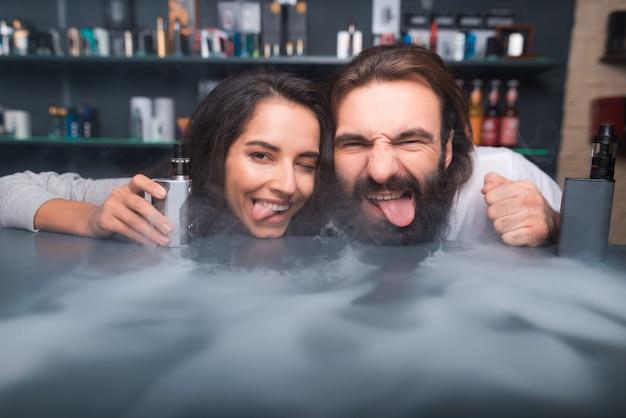 Uomo e donna che posano sulla macchina fotografica con la sigaretta elettronica.