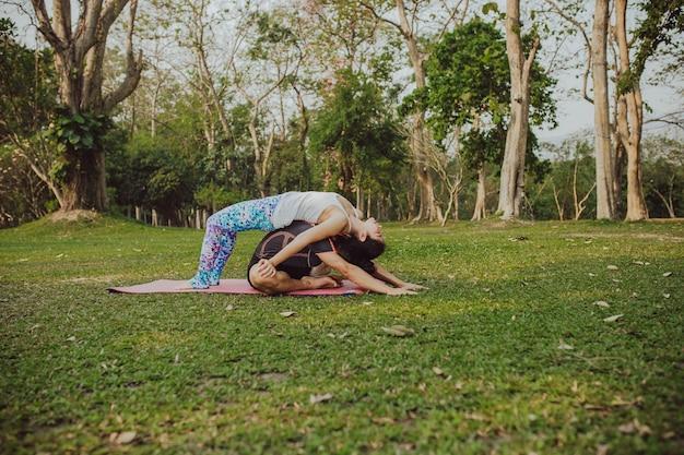 Uomo e donna che praticano yoga nel parco