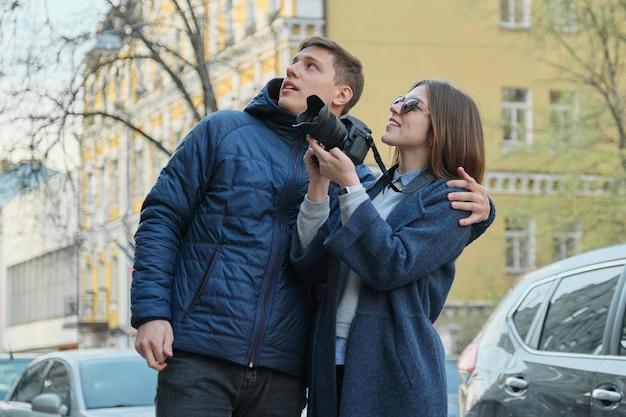 Uomo e donna che prendono le immagini sulla macchina fotografica