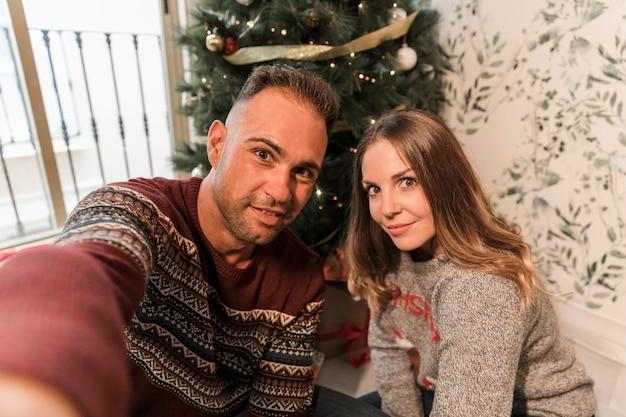 Uomo e donna che prendono selfie vicino all'albero di natale