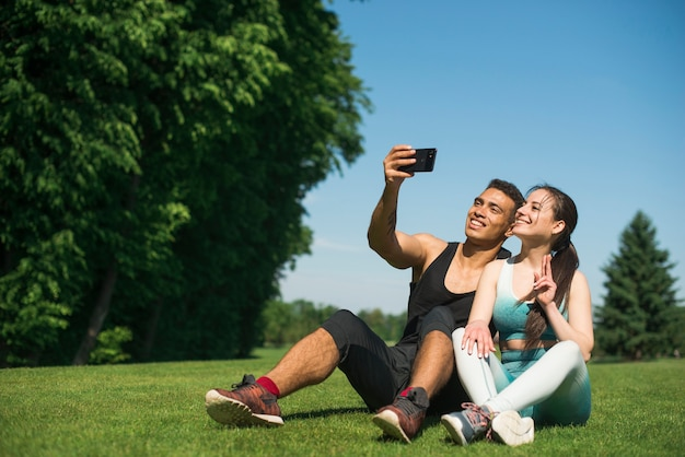 Uomo e donna che prendono un selfie in un parco
