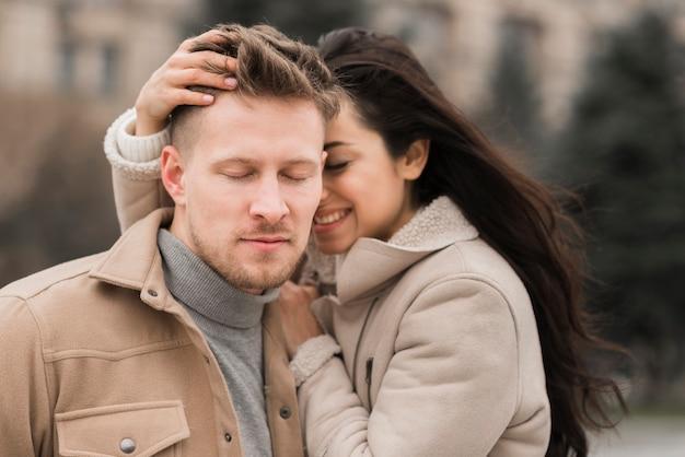 Uomo e donna che propongono all'aperto