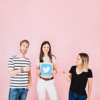Uomo e donna che punta al loro amico tenendo l'icona di twitter su sfondo rosa