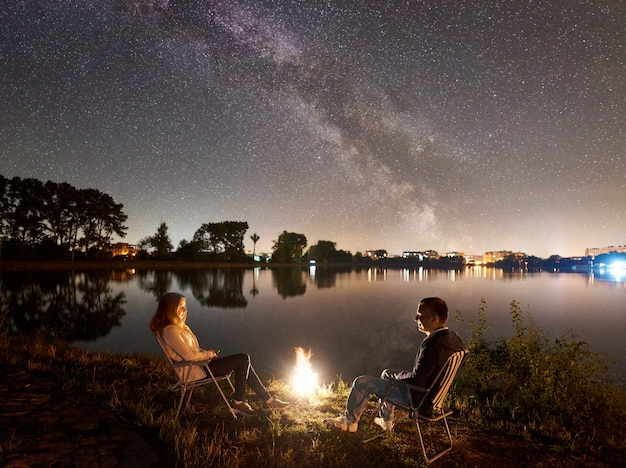 Uomo e donna che riposano sulla riva sotto il cielo notturno