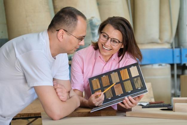 Uomo e donna che scelgono la lavorazione di finitura di mobili in legno