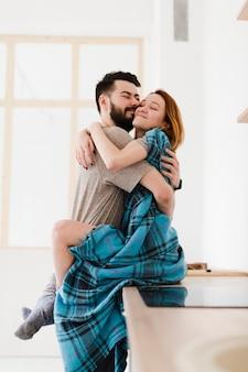 Uomo e donna che si abbracciano arredamento minimalista