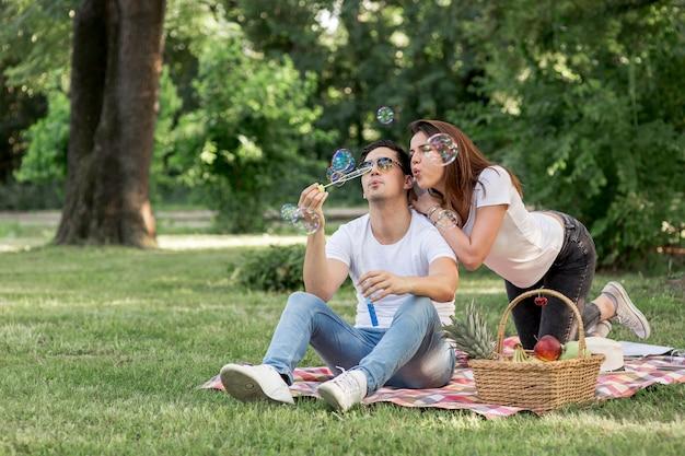 Uomo e donna che si divertono facendo bolle