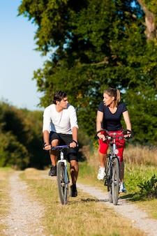 Uomo e donna che si esercitano con la bicicletta