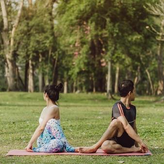 Uomo e donna che si estendono nel parco