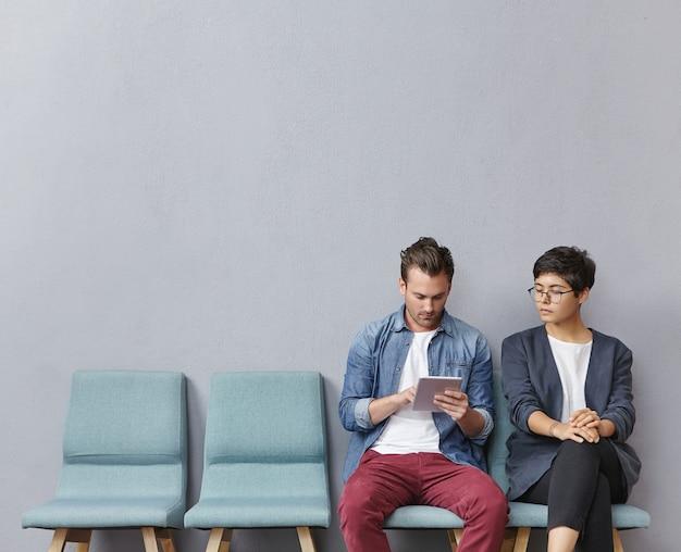 Uomo e donna che si siedono nella sala d'attesa