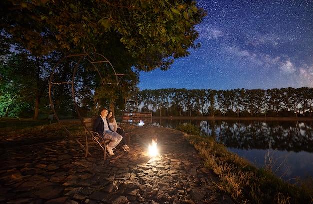 Uomo e donna che si siedono sul banco vicino al falò sulla riva vicino al lago sotto l'albero. coppia godendo della straordinaria vista del cielo serale pieno di stelle, via lattea e foresta sullo sfondo. concetto di stile di vita all'aperto