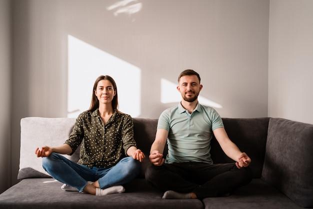 Uomo e donna che si siedono sul sofà nella posa del loto