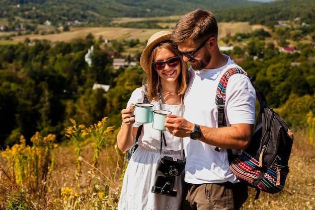 Uomo e donna che si tengono e che bevono caffè