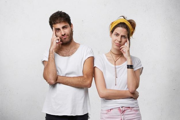 Uomo e donna che tengono le dita sulle tempie che riflettono da vicino su qualcosa mentre. ragazzo barbuto in piedi vicino a sua moglie pensando ai loro piani futuri