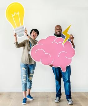 Uomo e donna che tengono rispettivamente le icone della lampadina e della nuvola rosa