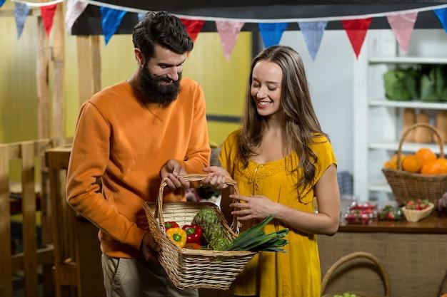 Uomo e donna che tengono un cestino delle verdure alla drogheria
