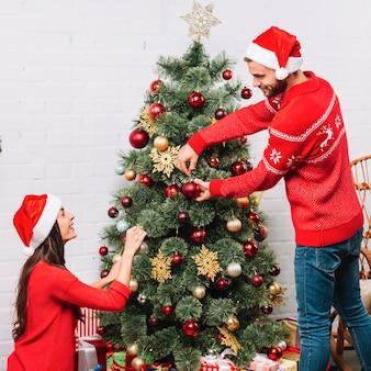 Uomo e donna che vestono l'albero di natale