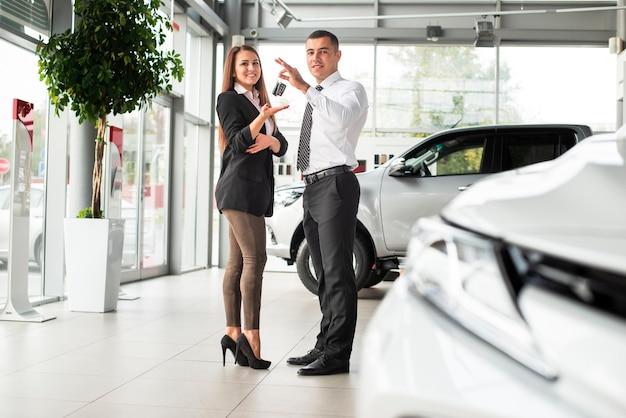 Uomo e donna chiudendo un affare di auto