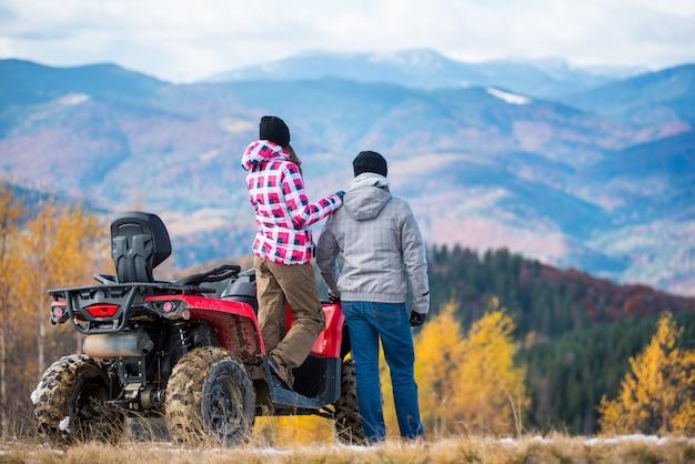 Uomo e donna con bici quad rossi in montagna