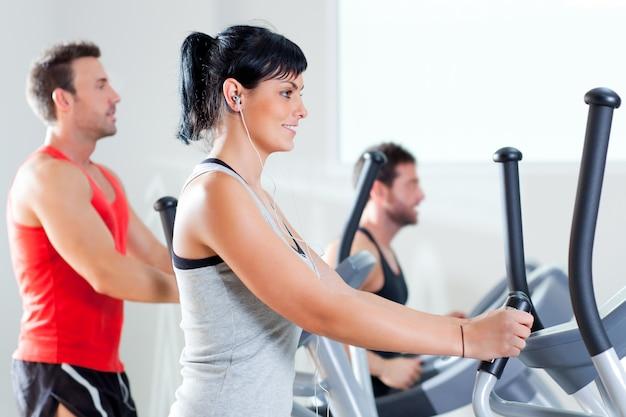 Uomo e donna con ellittica cross trainer in palestra
