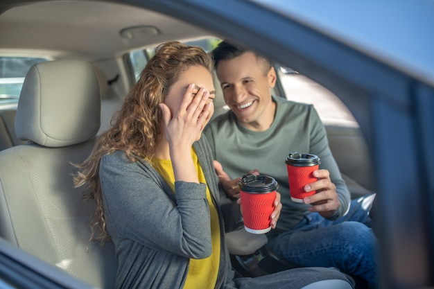 Uomo e donna con i bicchieri di plastica nelle mani in auto