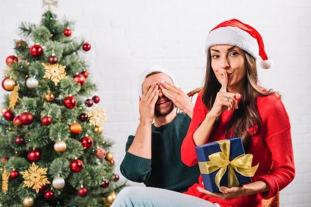 Uomo e donna con presente che si siede vicino all'albero di abete