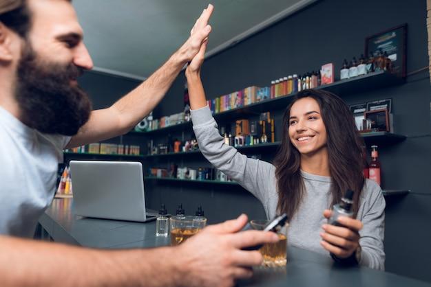 Uomo e donna con sigaretta elettronica in vapeshop.