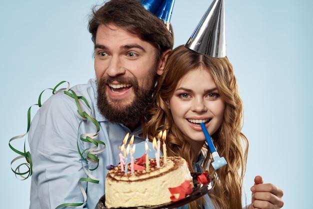 Uomo e donna con torta e candele in cappelli da festa