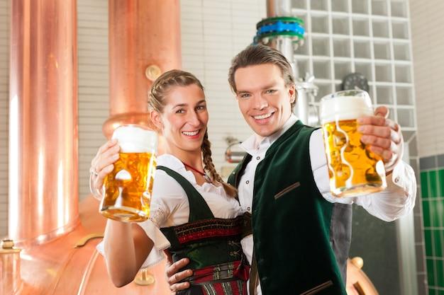 Uomo e donna con un bicchiere di birra nel birrificio