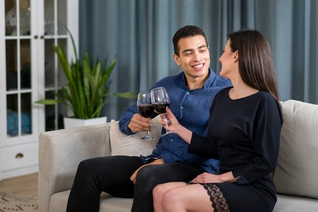 Uomo e donna con un bicchiere di vino, seduti sul divano