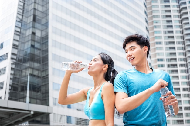 Uomo e donna, coppia d'amore, bevendo acqua fresca dopo runnin