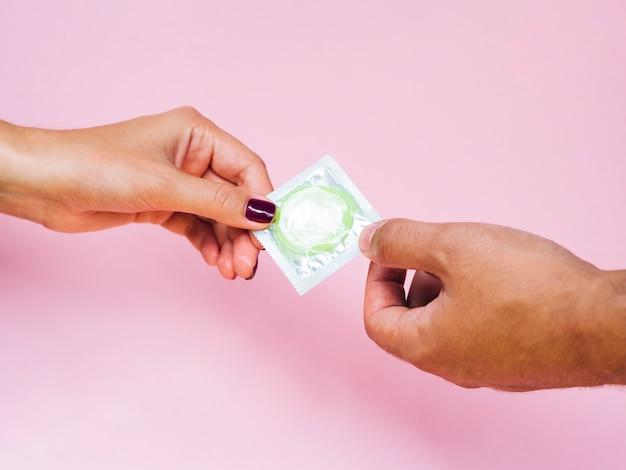 Uomo e donna del primo piano che tengono un preservativo verde