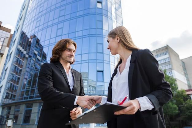 Uomo e donna di affari che agitano le mani