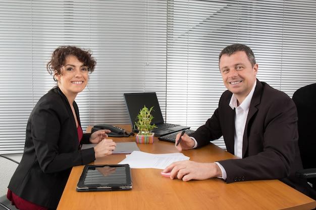Uomo e donna di affari che parlano insieme guardando il documento