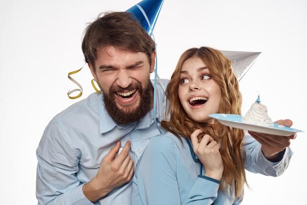 Uomo e donna di compleanno con un bigné e una candela in un cappello del partito, bianco