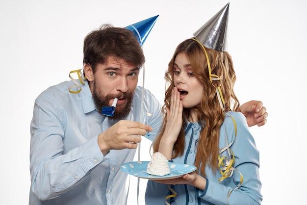 Uomo e donna di compleanno con un bigné e una candela in un cappello del partito, spazio bianco