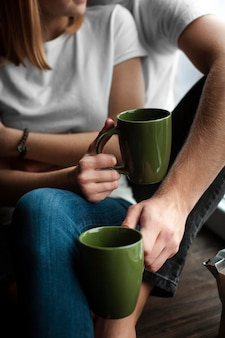 Uomo e donna di vista frontale che godono insieme del loro caffè