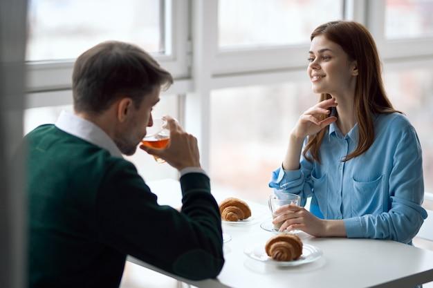 Uomo e donna felici nelle coppie amorose della prima colazione dei croissant del ristorante