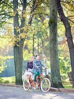 Uomo e donna in bicicletta tandem nel parco