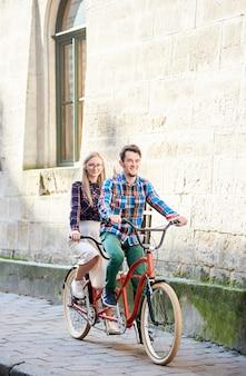 Uomo e donna in sella a una bicicletta tandem lungo la strada della città