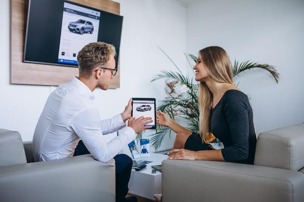 Uomo e donna in una sala d'esposizione dell'automobile facendo uso della compressa