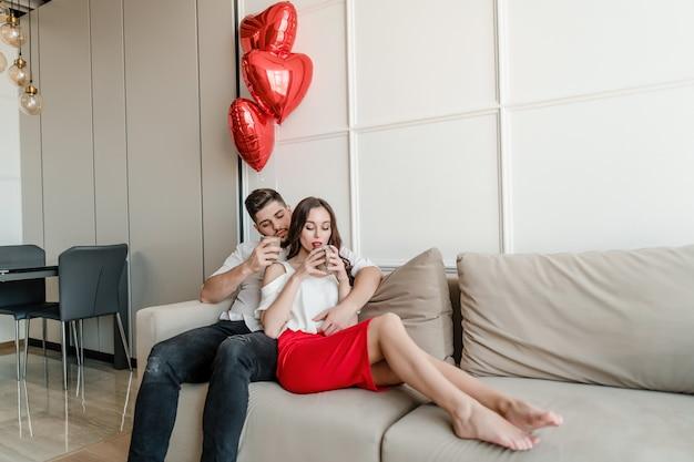 Uomo e donna innamorata che beve dalle tazze al mattino sul divano con palloncini a forma di cuore a casa