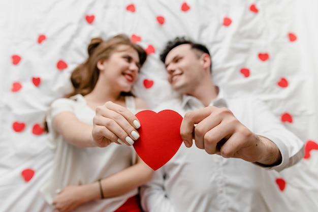 Uomo e donna innamorata nel letto con forme di cuore