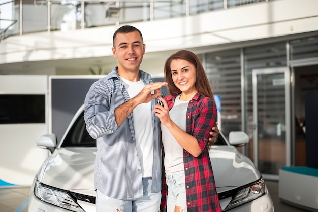 Uomo e donna insieme al concessionario auto