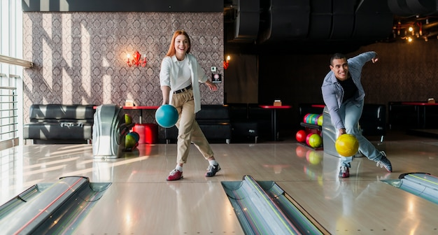 Uomo e donna lanciando palle da bowling sul vicolo