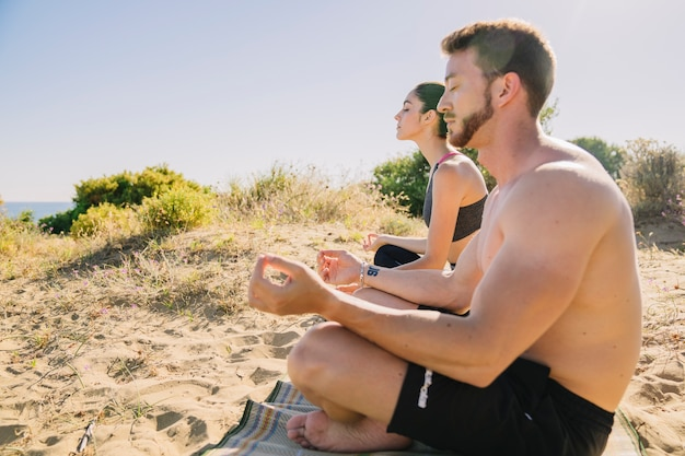 Uomo e donna meditando sulla spiaggia