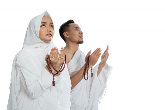 Uomo e donna musulmani che pregano in ihram tradizionale bianco dei vestiti