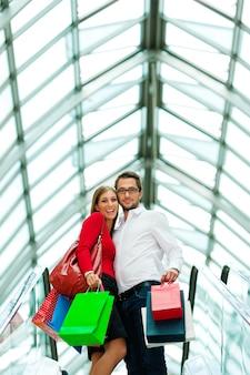 Uomo e donna nel centro commerciale con le borse