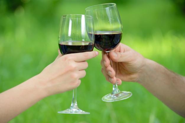 Uomo e donna, rilassarsi e bere vino nel parco.